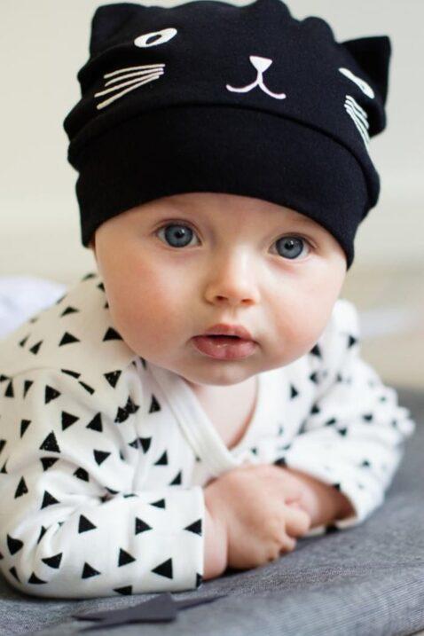 Junge trägt schwarze Baby Mütze mit Kätzchen Motiv und Ohren Babymütze & Katzenmütze unifarben - Wickelbody weiß Dreiecke langarm Langarmbody von Pinokio - Babyphoto seitlich