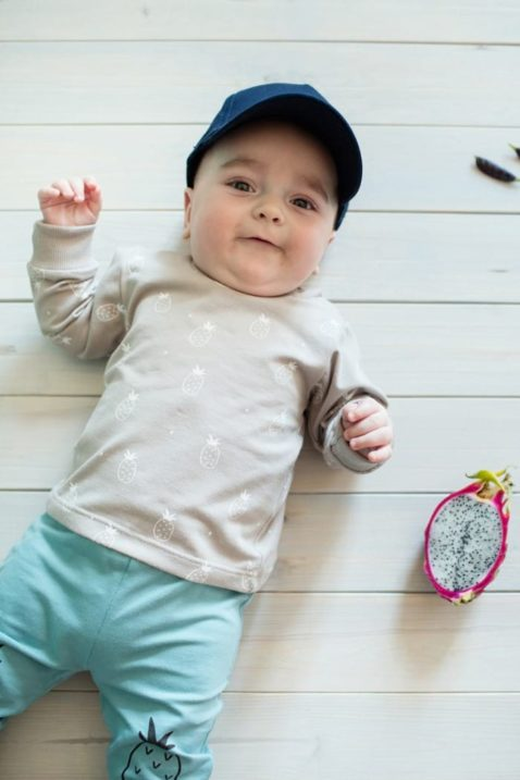 Lachendes Baby mit beigem Baby Langarmshirt & Ananas Motiven - Leichter Jungen & Mädchen Rundhals Pullover Sweatshirt langarm Oberteil von Pinokio - Vorderansicht
