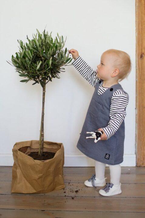 Spielendes Mädchen Baby mit grauem Latzkleid Sweatkleid ärmellos mit Patch, Brusttasche & Knöpfe im strukturierten Design mit schwarz-weiss-gestreiftem Oberteil von Pinokio - Babyphoto