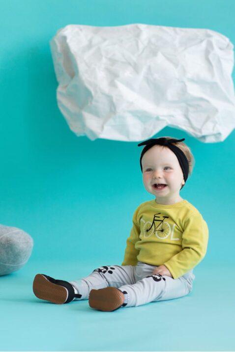 Sitzendes lachendes Baby mit grauer Baby Leggings Sweathose mit Hundetatzen & Schriftzug Have Fun, gelbes Langarmshirt Body langarm mit Fahrrad, schwarzes Stirnband & Babyschuhe für Jungen & Mädchen von Pinokio - Babyphoto