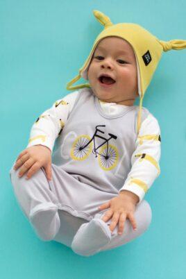 Lachendes liegendes Baby mit hellgrauem Baby Strampler mit Fuß & Fahrrad Motiv, weißem Hunde Oberteil, gelber Mütze - Jungen & Mädchen Strampelanzug & Babystrampler von Pinokio - Babyphoto