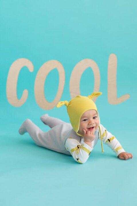 Liegendes krabbelndes lachendes Baby mit hellgrauem Baby Strampler mit Fuß & Fahrrad Motiv, gelber Mütze & weißem Body - Jungen & Mädchen Strampelanzug & Babystrampler von Pinokio - Set Inspiration