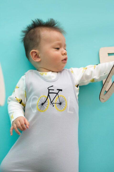 Liegendes spielendes Baby mit hellgrauem Baby Strampler mit Fuß & Fahrrad Motiv & weißem Oberteil - Jungen & Mädchen Strampelanzug & Babystrampler von Pinokio - Babyphoto