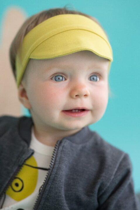 Lachendes Baby mit dunkelgrauer Zip Sweatjacke Pullover strukturiert mit Taschen & Patch, gelber Schildmütze, weißem Hunde Oberteil Body für Jungen & Mädchen von Pinokio - Babyphoto