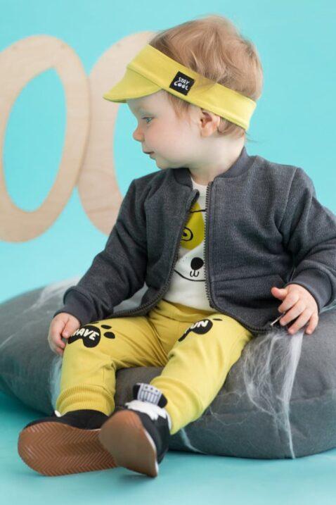 Sitzendes Baby mit dunkelgrauer Zip Sweatjacke Pullover strukturiert mit Taschen & Patch, gelber Leggings & Schildmütze, weißem Hunde Body für Jungen & Mädchen von Pinokio - Babyphoto