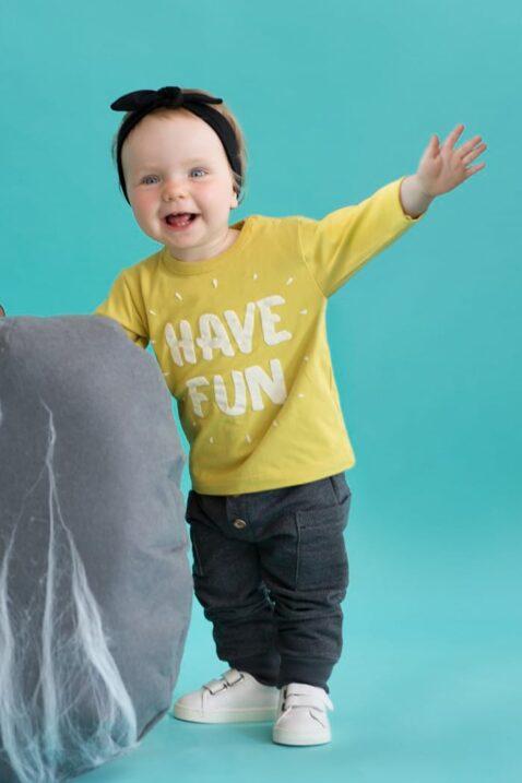 Stehendes lachendes Baby Mädchen mit gelbem Baby Langarmshirt Sweatshirt mit HAVE FUN Flockdruck, grauer Babyhose, schwarzem Stirnband, weißer Babyschuhe von Pinokio - Set Inspiration