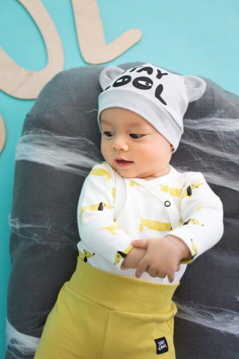 Liegendes lachendes Baby Junge mit gelber Strampelhose mit Füßen & Stay Cool Patch, grauer Mütze & weißem Wickelbody Hund - Senfgelbe Schlafhose, Babyhose & Stramplerhose von Pinokio - Babyphoto