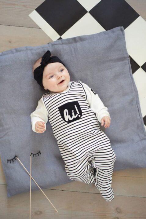 Liegendes lachendes Baby Mädchen mit schwarz-weiß gestreiftem Baby Strampler mit Fuß & Tasche, weißem Oberteil, schwarzem Stirnband - Strampelanzug von Pinokio - Babyphoto