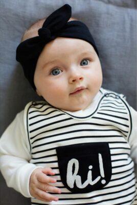 Liegendes süßes Baby Mädchen mit schwarz-weiß gestreiftem Baby Strampler mit Fuß & Tasche, weißem Oberteil, schwarzem Stirnband - Babystrampler von Pinokio - Babyphoto