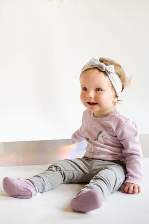 Lachendes & sitzendes Baby Mädchen mit rosa Baby Body langarm & Einhorn Motiv, grauer Babyhose, grauem Stirnband & rosa Babyschuhe - Rosa Baumwoll Langarmbody & Babybody von Pinokio - Babyphoto