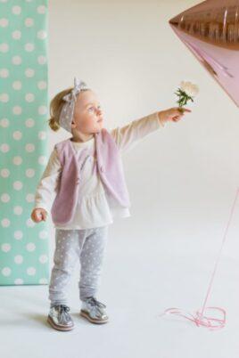 Süßes stehendes Mädchen mit Blume in der Hand trägt graue Baby Leggings Sweathose mit weißen Punkten & Patch, graues Stirnband & Weste, weißes langarm Tunika Shirt Oberteil & silberne Babyschuhe von Pinokio - Babyphoto