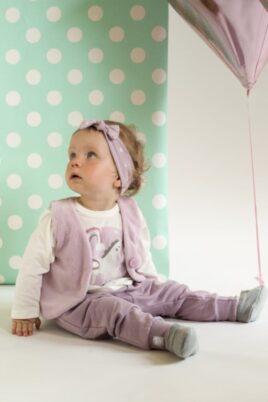 Süßes sitzendes Mädchen trägt rosa Baby Pumphose Haremshose mit Taschen & Patch, rosa Stirnband & Weste, weißes Langarmshirt Einhorn Oberteil & graue Babyschuhe von Pinokio - Babyphoto