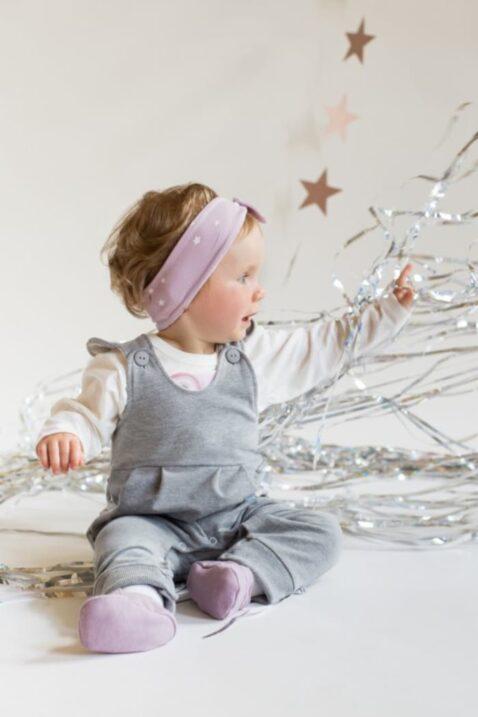 Sitzendes spielendes Mädchen Baby trägt rosa Stirnband Haarband mit weißen Sternen & Zierschleife, graue Latzhose, weißes Einhorn Oberteil Langarmshirt & rosa Babyschuhe von Pinokio - Babyphoto