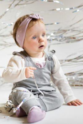 Süßes sitzendes staunendes Mädchen Baby trägt rosa Stirnband Haarband mit Schleife & weißen Sternen, graue Latzhose, weißes Oberteil Shirt langarm Einhorn & rosa Babyschuhe von Pinokio - Babyphoto