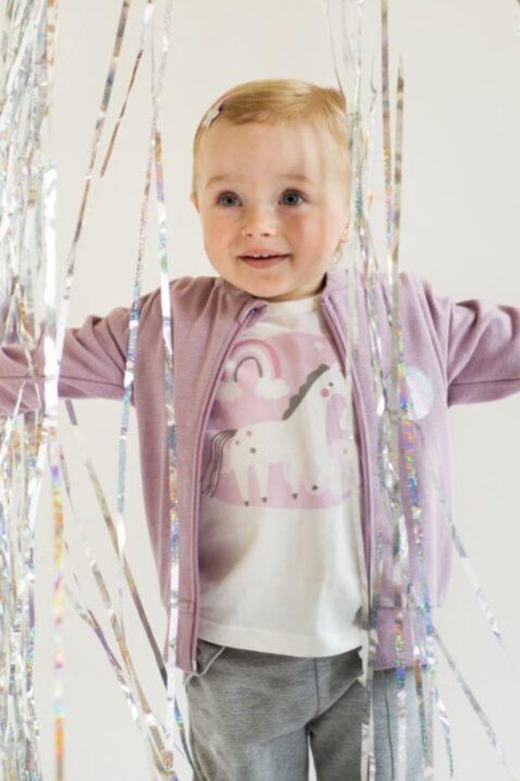 Süßes lachendes & stehendes Mädchen mit kurzen Haaren trägt weißes Baby Langarmshirt Rundhals Oberteil mit Einhorn Motiv, graue Babyhose & rosa Sweatjacke Einhorn von Pinokio - Babyphoto