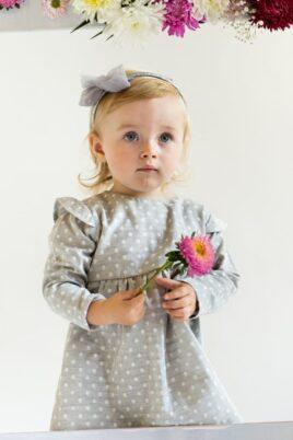 Stehendes Mädchen mit Blume & kurzen Haaren trägt graues Baby Langarmkleid Babykleid aus Baumwolle mit Rüschen & weißen Punkten All-over-Muster und graues gepunktetes Haarband Polka Dot von Pinokio - Babyphoto