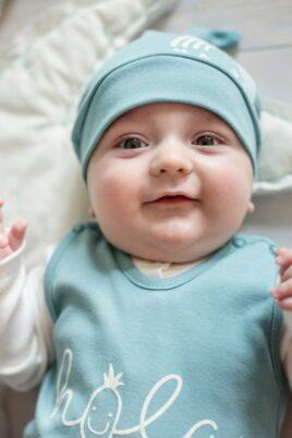 Lachendes & liegendes Baby Junge trägt grüne Mütze mit kleinem Knoten an der Spitze, grüner Strampler mit Schrifzug HOLA & weißem Wickelbody Oberteil von Pinokio - Babyphoto