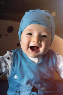 Lachender glücklicher Junge trägt blaue Baby Mütze mit Weltall Motiven Sterne Raketen Mond, blauer Weltraum Strampler & weißes Oberteil von Pinokio - Babyhoto