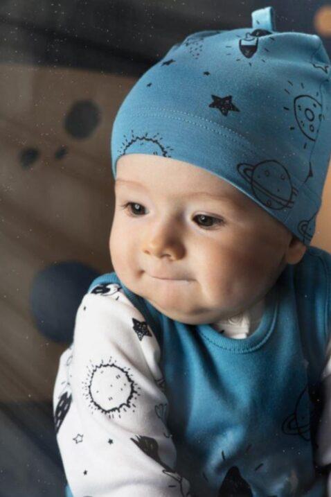Sitzender Junge trägt blaue Baby Mütze mit Weltall Sterne Raketen Mond Motiven, blauer Strampler Weltraum & weißes Cardigan Oberteil von Pinokio - Babyhoto