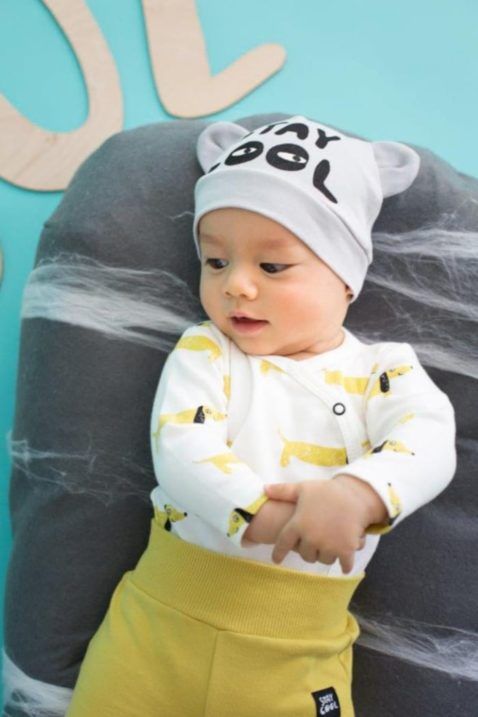 Baby lachender liegender Junge trägt graue Baby Mütze mit Ohren & Schriftzug Stay Cool, weißen Wickelbody mit Hunden & gelbe Strampelhose Schlafhose mit Patch von Pinokio - Babyphoto