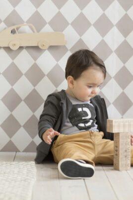 Spielender sitzender Junge trägt grauen Baby Langarmbody mit Oldtimer Rennwagen Autoschild Autonummer schwarz-weiß, dunkelgraue Babyjacke, schwarze Babyschuhe & beige Babyhose von Pinokio - Babyphoto