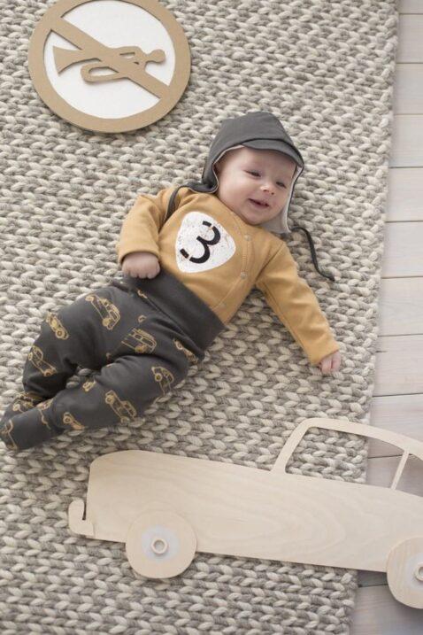 Liegender lachender Junge trägt braunen Baby Wickelbody langarm Langarmbody mit Oldtimer Rennwagen Autoschild, braune Strampelhose Rennwagen, braune Fliegermütze Schirmmütze mit Bindeband & Ohrenklappen von Pinokio - Babyphoto