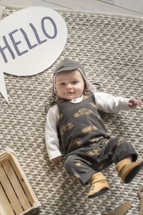 Lachender liegender Junge trägt graphit grauen Baby Strampler mit Fuß & Oldtimer Rennwagen Auto Motive, braune Baby Fliegermütze mit Bindeband & Ohrenklappen, hellbraune Babyschuhe von Pinokio - Babyphoto