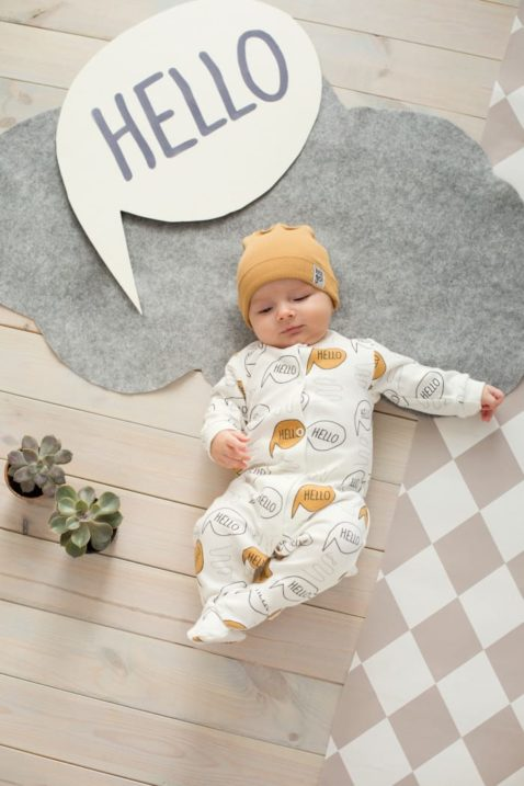 Schlafender Junge trägt braune Baby Baumwoll Mütze mit Umschlag & Patch Let´s go für den Frühling, Sommer, Herbst & Winter - weißen Schlafoverall Oldtimer mit Hello Schriftzüge Motive von Pinokio - Babyphoto