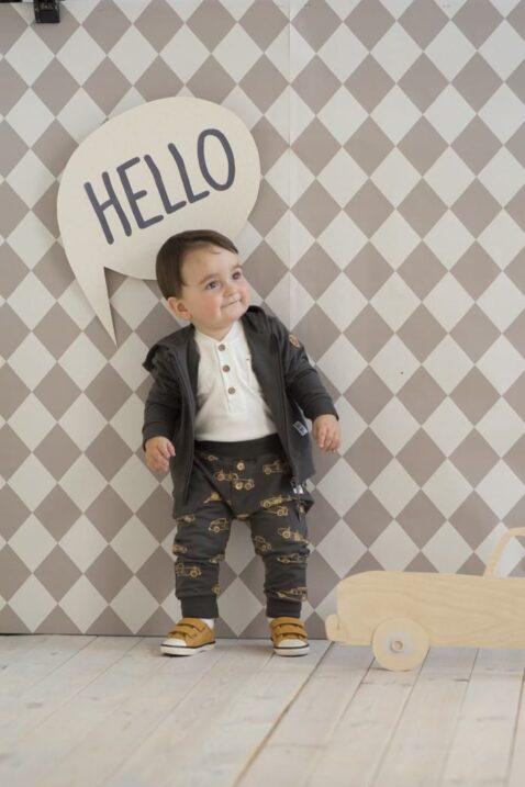 Staunender Junge trägt Baby Kapuzen-Sweatjacke Pullover mit Oldtimer Rennwagen & Patch Let´s go Vintage Cars, dunkelgraue braune Baumwoll Babyhose mit Rennautos & ockerfarbene braune Babyschuhe von Pinokio - Babyphoto