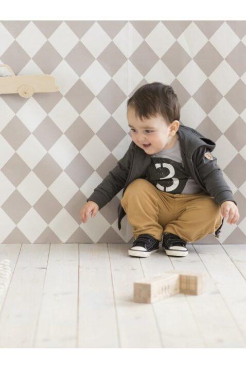 Lachender Junge trägt hellbraune Babyhose im Retro Vintage Look mit Taschen, Holzknöpfe & Patch Oldtimer Autos, graue dunkle Kapuzen Sweatjacke Pullover mit Reißverschluss & schwarze Babyschuhe von Pinokio - Babyphoto
