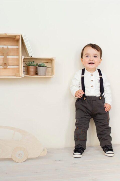 Lachender Junge trägt graue Babyhose mit Taschen & Hosenträgern abnehmbar verstellbar & langarm Oberteil Polo mit Knöpfe in Holzoptik im Vintage Retro Oldtimer Auto Look von Pinokio - Babyphoto