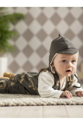 Staunender krabbelnder Junge trägt graue Baby Fliegermütze mit Schirm Schild, Bindeband, Ohrenklappen - weißes Baby Oberteil Baumwolle - dunkelgrauer Strampler mit Füßen im Vintage Retro Oldtimer Auto Rennwagen Design von Pinokio - Babyphoto