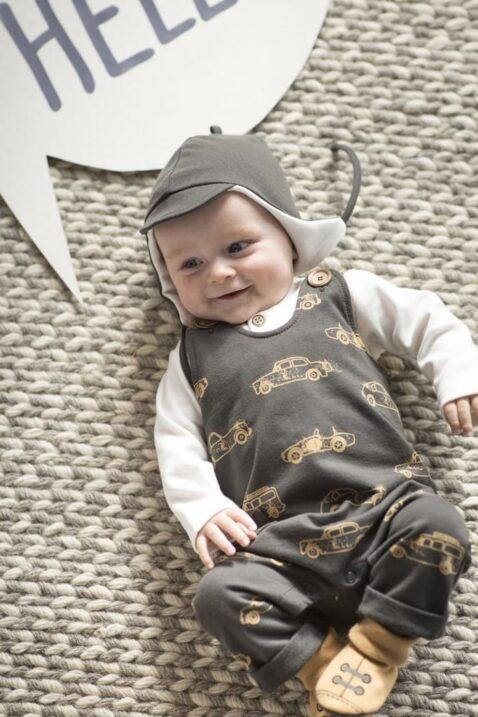 Liegender lachender Junge trägt dunkelgrauen Baby Strampler mit Fuß & Oldtimer Retro Auto Rennwagen Motive, braune Baby Pilotenmütze Fliegermütze mit Bindeband & Ohrenklappen, weißes Oberteil & hellbraune Hausschuhe Babyschuhe Baumwollschuhe von Pinokio - Babyphoto