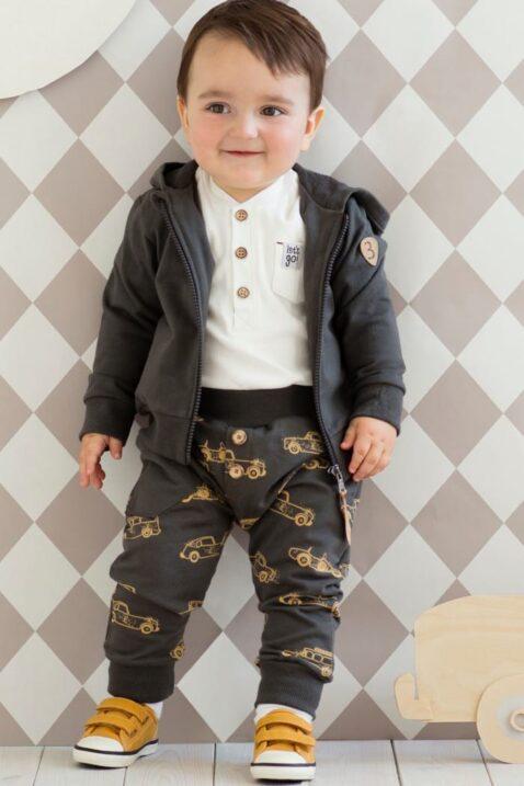 Lächelnder Junge trägt graue Baby Pumphose Haremshose Schlupfhose mit Autos Oldtimer Sportwagen Motiven & Tasche, weißes lamgarm Oberteil Polo, dunkelgrauer Zip Kapuzenpullover Sweatjacke mit Rennwagen & braune Babyschuhe von Pinokio - Babyphoto Vorderansicht