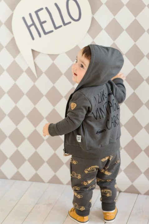 Staunender Junge trägt graue Baby Pumphose Haremshose Schlupfhose mit Autos Oldtimer Sportwagen Rennwagen Motiven & Tasche, dunkelgraue Babyjacke Kapuzen-Sweatjacke Autos, braune Babyschuhe von Pinokio - Babyphoto Rückenansicht