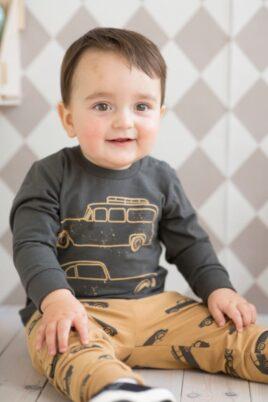 Sitzender lächelnder Junge hellbraune Baby Leggings Sweathose mit Autos Oldtimer Sportwagen Motiven, graues langarm Oberteil Langarmshirt Sweatshirt mit Autos Formel 1 Rennwagen von Pinokio - Babyphoto
