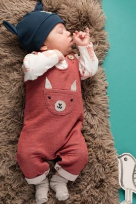 Schlafender Junge trägt bordeaux rote Lama Baby Latzhose mit Brusttasche Lama mit Ohren, kontraststarken Holz Knöpfe & Beinumschlag - weißer langarm Wickelbody Lama - graue babysöckchen - dunkelblaue Zipfelmütze mit Happy Lama von Pinokio - Babyphoto