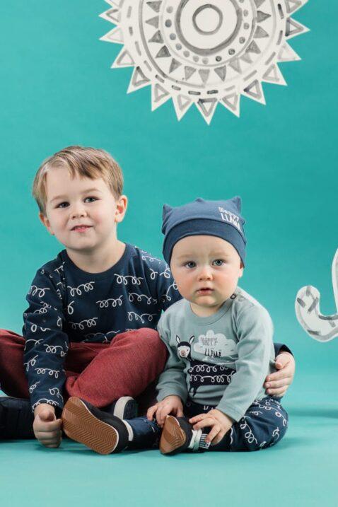 Gruppe von 2 sitzende Baby Jungen Kinder tragen Kollektion Happy Lama von Pinokio - Größerer Junge trägt rote Pumphose, blaues Oberteil mit Lama Motiv Baumwolle - Baby Junge trägt blaue Mütze, grünen Body & blaue Leggings im Lama Design von Pinokio - Babyphoto