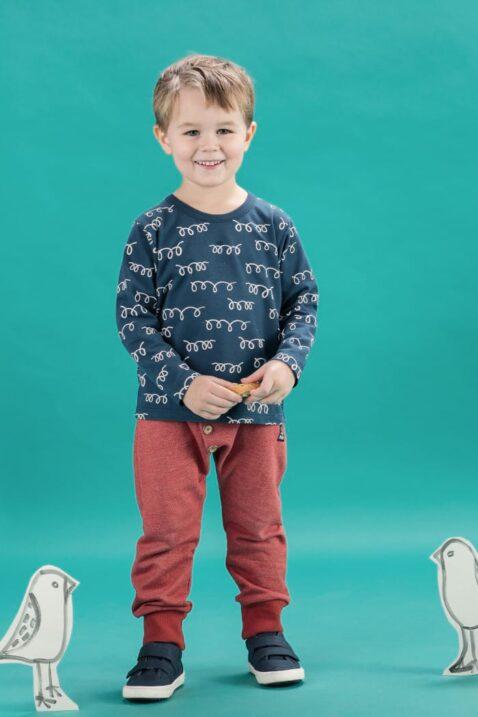 Stehender lächelnder Junge trägt rote Baby Pumphose Sweatpants Haremshose mit Patch Be Happy strukturiert - blaues Oberteil Langarmshirt Sweatshirt Lama Wolle Motiv - navyblaue Babyschuhe von Pinokio - Babyphoto