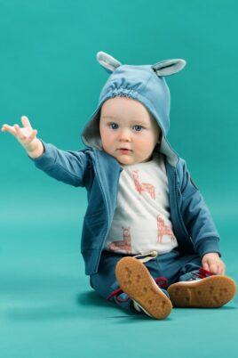 Sitzender Junge trägt weißen Baby Body ärmellos ohne Ärmel mit Lama Motiven - Blaue Baby Sweatjacke Kapuzenjacke langarm mit Lama Ohren - Blaue Babyhose mit Taschen & Happy Lama Patch von Pinokio - Babyphoto