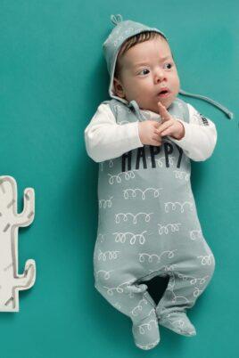 Liegender Junge trägt grünen Baby Strampler mit Füßen & Lama Motiv Happy Strampelanzug - Grüne Babymütze Lama Baumwollmütze mit Kordeln Kinnbändchen & Ohrenschutz Ohrenklappen - Weisses Oberteil langarm Babyjäckchen Body mit Lama Patch von Pinokio - Babyphoto