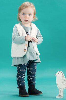 Stehendes Mädchen trägt blaue Baby Leggings Schlupfhose Sweathose mit Schleifen & Kringel im Lama Look - grüne Tunika Oberteil mit Lama Motiv langarm - weiße Weste aermellos im Lamawolle Design - blaue Babyschuhe Winter von Pinokio - Babyphoto