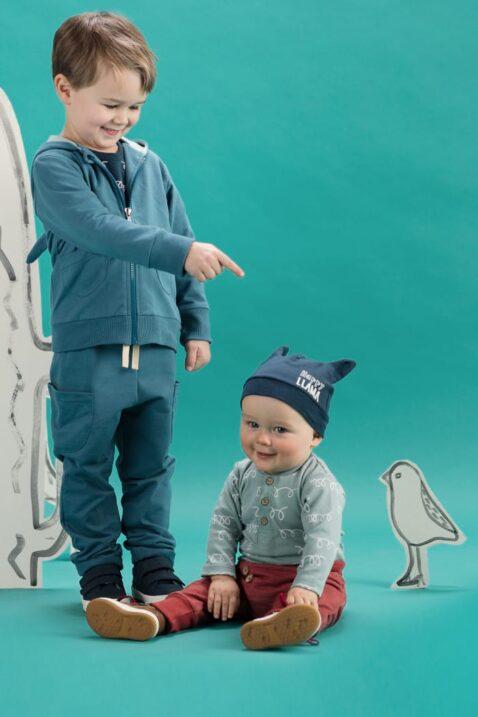 Zwei Jungs - Baby Junge sitzt & trägt Polobody langarm ohne Kragen, blaue Lama Babymütze mit Ohren & rote Pumphose mit Lama Patch - Großer Junge steht & trägt grün türkise Babyhose mit Taschen, Kapuzenjacke Swetjacke mit Lama-Ohren Kapuze & Reißverschluss in Türkis Grün von Pinokio - Set Inspiration Babyphoto Kinderphoto