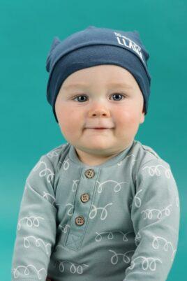 Junge trägt grünen türkisen Baby Polobody langarm Polo ohne Kragen, Holz Knöpfe Knopfleiste & weiße Kringel Schleifen Lama Wolle Motiv - Blaue Kinder Lama Motiv Babymütze mit Ohren von Pinokio - Babyphoto