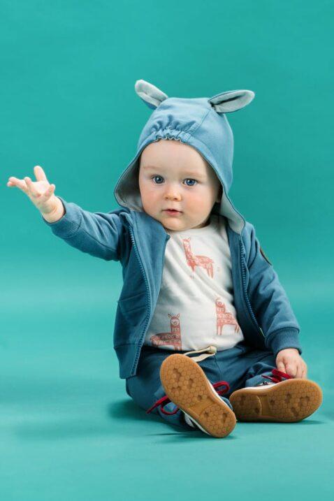 Sitzender staunender Baby Junge trägt blaue Babyhose Sweathose mit Taschen, Patch Be Happy & Kordel - Blau grünen Kapuzenpullover Kapuzen Sweatjacke mit Ohren, Reißverschluss & Lama Patch aus Leder - Weißen Body ärmellos ohne Ärmel Oberteil mit Lamas von Pinokio - Babyphoto