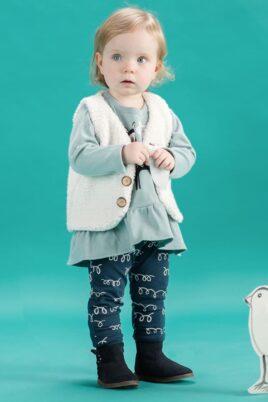 Stehendes staunendes Baby Mädchen trägt Langarmshirt Tunika in Kleidchenoptik mit Lama Motiv - weiße ärmellose Weste im Lama Wolle Design - blaue Leggings mit Schleifen Lama Wolle - blaue Babyschuhe Winter von Pinokio - Babyphoto