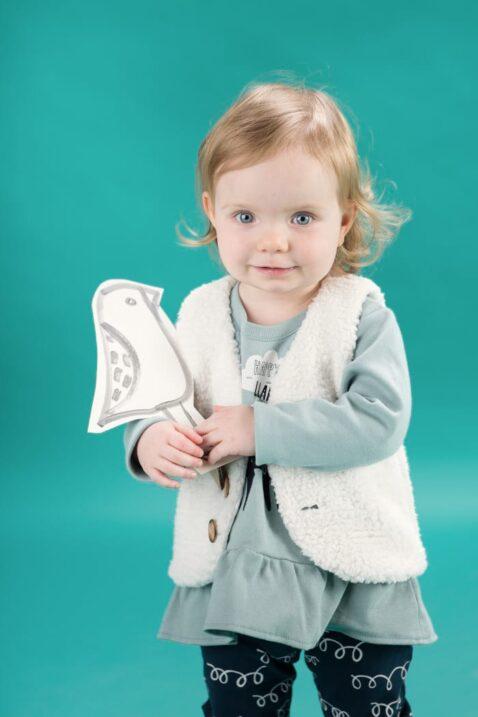 Stehendes lächelndes Baby Mädchen trägt Tunika Kleid Langarmshirt in Kleidchenoptik mit Lama Motiv - weiße gefütterte Weste ohne Ärmel mit Holz Knöpfe im Lama Wolle Design - blaue Leggings Schlupfhose mit Schleifen Lama Wolle Design von Pinokio - Babyphoto