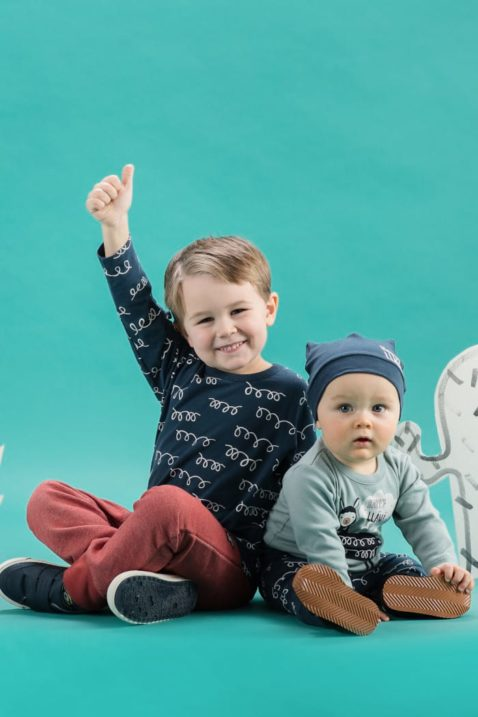 Zwei sitzende kleine Kinder - der größere lachende Junge trägt ein blaues Baby Langarmshirt Longsleeve mit weissen Schleifen & roter Lama Pumphose - kleiner staunender Junge trägt blaue Lama Babymütze mit Ohren, grünen Lagarmbody Lama Motiv & blaue Leggings Schlupfhose mit Schleifen Kringel Lamawolle Optik von Pinokio - Babyphoto Kinderphoto