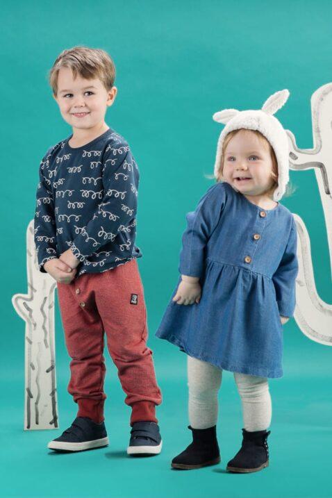 Zwei stehende kleine Kinder - der größere lachende Junge trägt ein blaues Baby Longsleeve Shirt langarm mit weissen Schleifen & roter Lama Pumphose - das lachende Mädchen trägt ein Langarm Kleid in Jeans-Optik Denim Look & eine weiße Lama Mütze mit Ohren von Pinokio - Babyphoto Kinderphoto