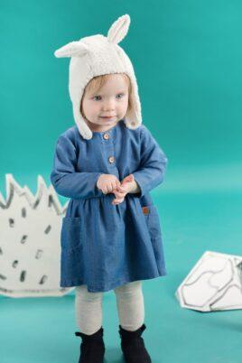 Stehendes staunendes Baby Mädchen trägt weiße gefütterte warme Babymütze mit Ohren & verstellbaren Ohrenklappen im Lama Design Hasenohren - blaues Langarm Kleid mit Taschen & Leder-Patch im Blue Denim Jeans Look - graue Strumpfhose - blaue Winter Babyschuhe von Pinokio - Babyphoto